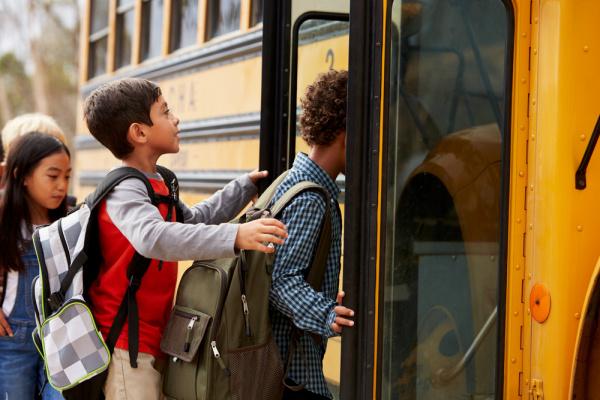 kids getting onto a school bus